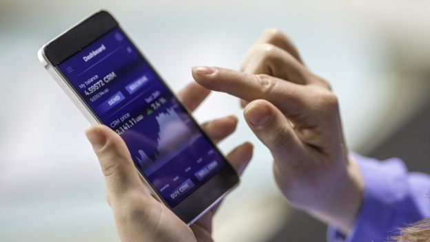 Celular con cirptomonedas en la pantalla